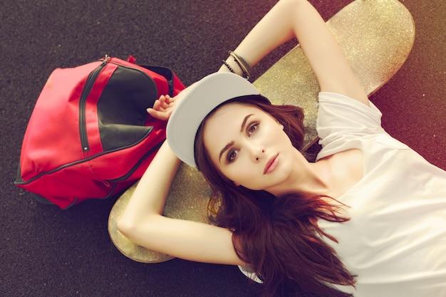 Vista de cima da menina descansando em seu skate Foto gratuita