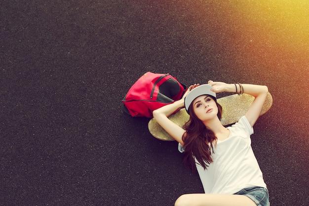 Vista de cima da mulher deitada no chão com skate Foto gratuita