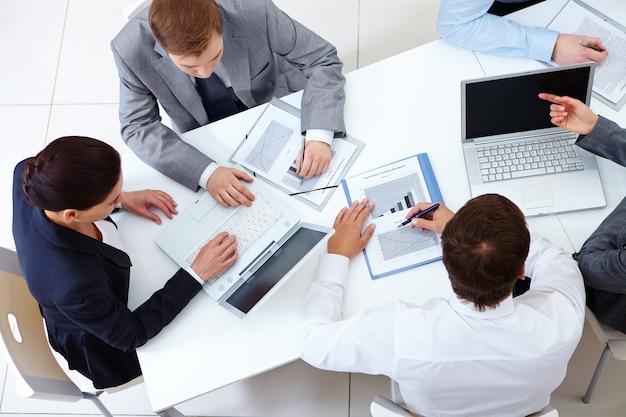Vista de cima de colegas de trabalho planejamento de uma estratégia Foto gratuita