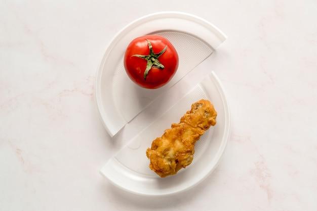 Vista de cima de frango frito e tomate vermelho inteiro no prato quebrado Foto gratuita