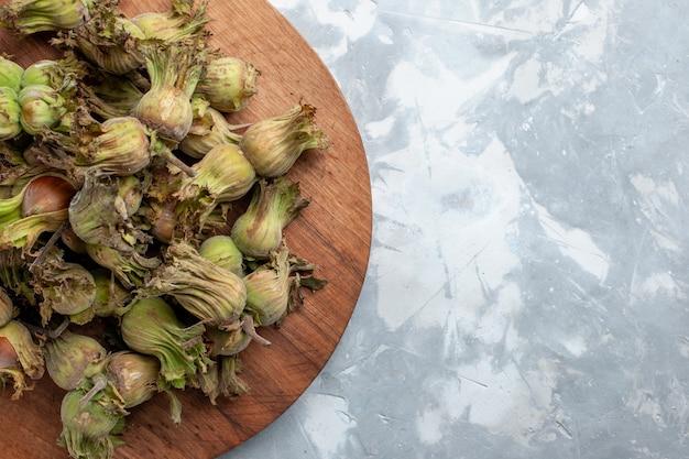 Vista de cima de perto avelãs inteiras frescas com cascas de nogueira, porca de mesa branca Foto gratuita