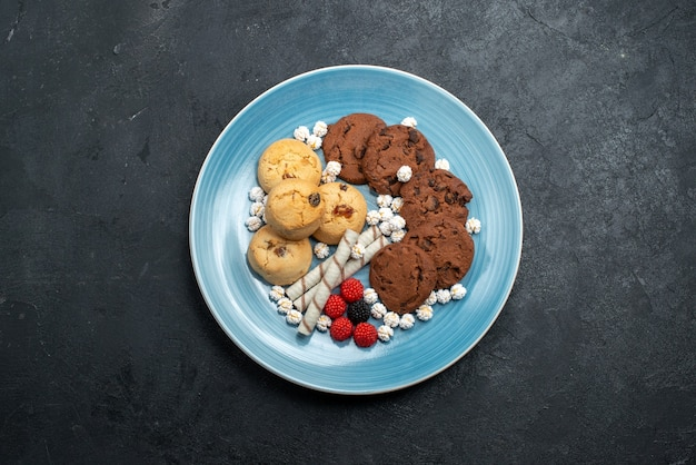 Vista de cima deliciosos biscoitos de chocolate e simples com doces em uma superfície cinza escura bolo de biscoito de açúcar biscoito doce Foto gratuita