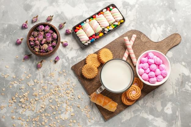 Vista de cima diferentes biscoitos com marshmallow e doces na superfície branca açúcar biscoito doce bolo guloseima bombom doce Foto gratuita