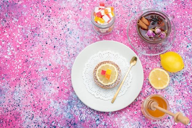 Vista de cima do bolo dentro do prato com chá de geleia de limão no fundo colorido bolo biscoito açúcar doce Foto gratuita