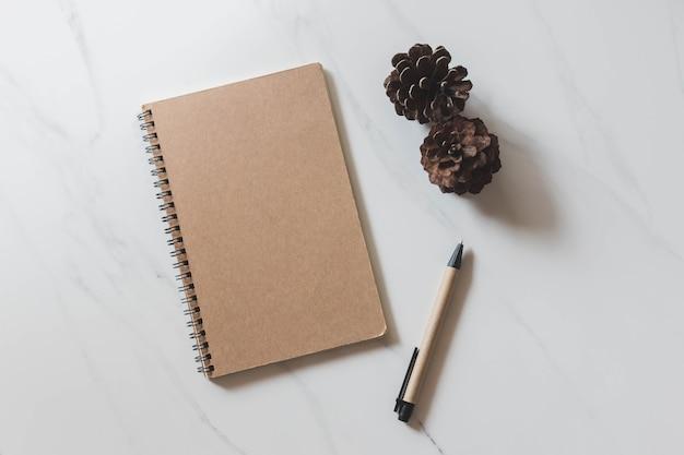 Vista de cima do caderno com cone de pinho e caneta no fundo de mesa de mármore branco Foto Premium