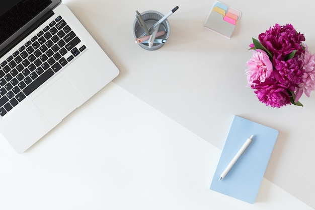 Vista de cima do local de trabalho de negócios de mulher com teclado de computador, notebook, buquê de flores de peônia rosa e telefone móvel, configuração plana. Foto Premium