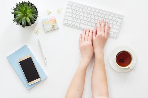 Vista de cima do local de trabalho de negócios de mulher com teclado de computador, notebook, flor em vaso verde e telefone móvel, configuração plana. Foto Premium