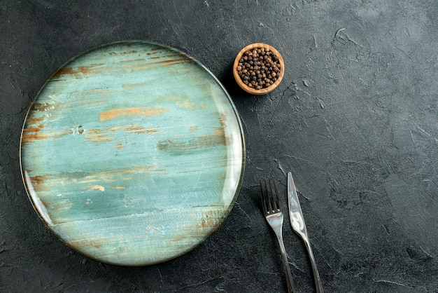 Vista de cima faca redonda de prato e garfo pimenta preta em uma tigela na mesa preta espaço livre Foto gratuita