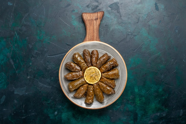Vista de cima folha dolma deliciosa refeição de carne oriental enrolada dentro de folhas verdes na mesa azul escuro refeição de carne comida jantar prato vegetais saúde caloria Foto gratuita