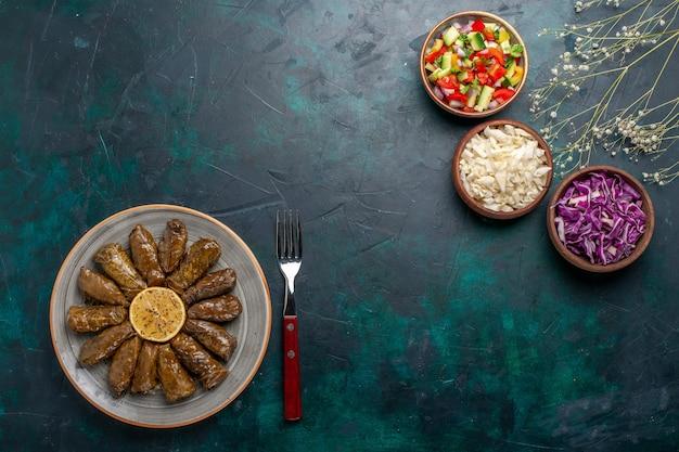 Vista de cima folha dolma refeição de carne oriental enrolada dentro de folhas verdes com vegetais fatiados em mesa de mesa azul prato de jantar refeição oriental Foto gratuita