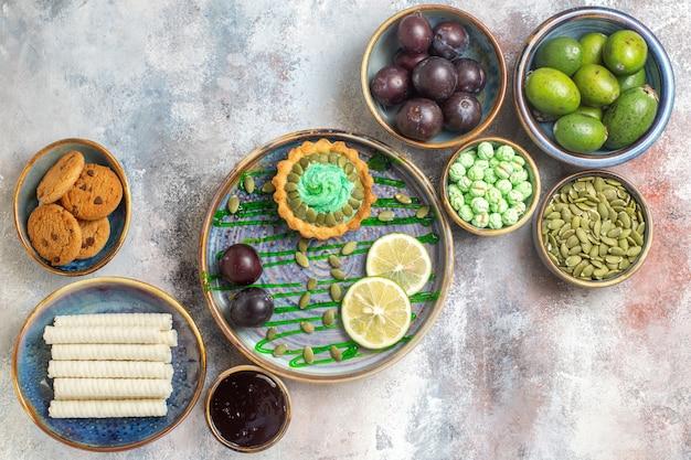 Vista de cima frutas frescas com biscoitos e bolinho Foto gratuita