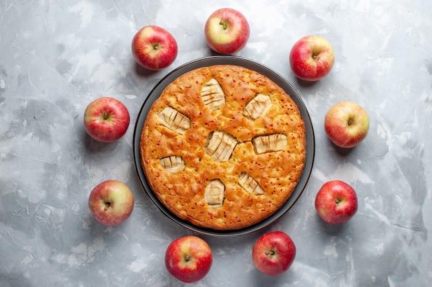Vista de cima maçãs vermelhas frescas formando um círculo com torta de maçã no fundo branco frutas frescas maduras vitamina Foto gratuita