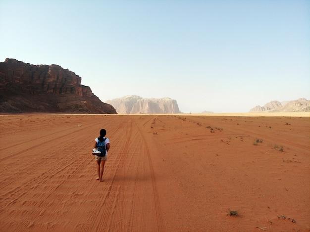 Vista de cima no enorme, vermelho, quente e muito deserto deserto wadi rum e young lady andando. reino da jordânia, país árabe na ásia ocidental Foto Premium