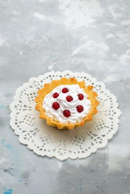 Vista de cima pequeno bolo delicioso com creme e frutas vermelhas na superfície cinza doce Foto gratuita