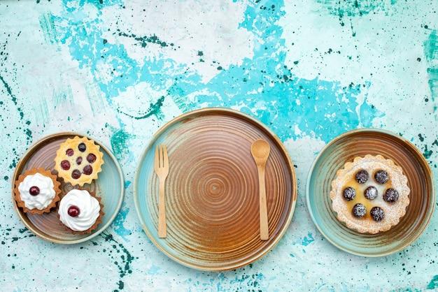 Vista de cima pequenos bolos deliciosos com creme e frutas no fundo azul claro bolo doce creme asse frutas Foto gratuita