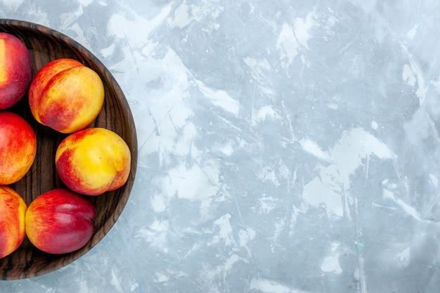 Vista de cima pêssegos frescos e frutas saborosas em um prato marrom sobre a mesa branca clara Foto gratuita