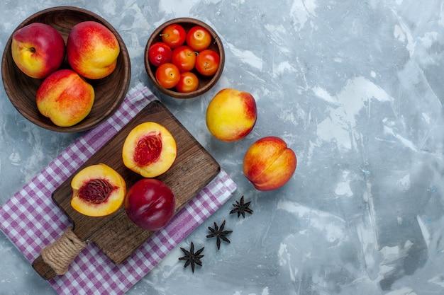 Vista de cima pêssegos frescos frutos maduros e saborosos dentro do prato marrom na superfície branca clara Foto gratuita