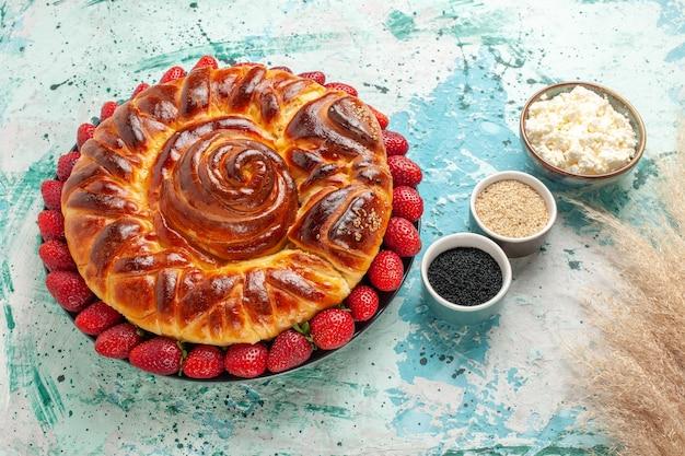 Vista de cima redonda deliciosa torta com morangos frescos na superfície azul Foto gratuita