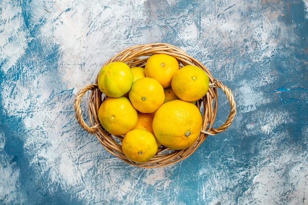 Vista de cima tangerinas frescas na cesta de vime no espaço da cópia da superfície azul e branca Foto gratuita
