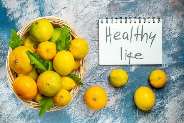 Vista de cima tangerinas frescas na cesta de vime, vida saudável, escritas no bloco de notas na superfície azul e branca Foto gratuita