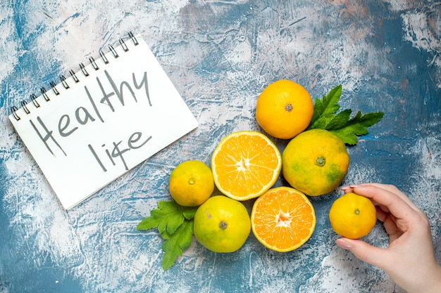 Vista de cima, tangerinas frescas, vida saudável, escritas no bloco de notas, mão feminina, segurando mandarim na superfície azul e branca Foto gratuita