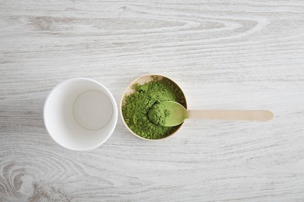 Vista de cima tira o vidro de papel branco e o chá matcha orgânico premium do japão na mesa de madeira, pronto para a preparação do café com leite de maneira moderna. primeira etapa da apresentação. tomando uma colher de chá de pó verde. Foto gratuita