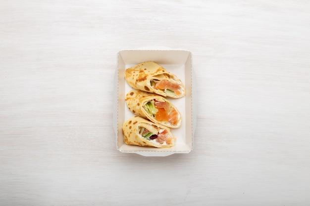 Vista de cima três fatias de panquecas com peixe vermelho, verduras e queijo em uma lancheira em um fundo branco Foto Premium