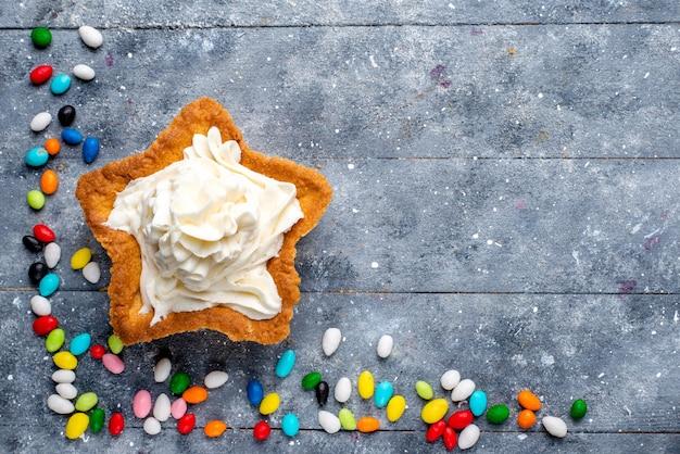 Vista de cima um pequeno bolo gostoso com creme e diferentes doces coloridos em todo o fundo claro doce doce açúcar cor bolo Foto gratuita