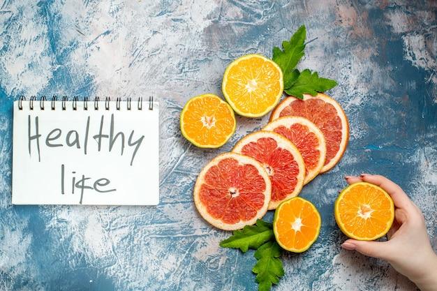 Vista de cima, vida saudável escrita no bloco de notas, corte de laranjas e toranjas, mão feminina segurando tangerina cortada na superfície azul e branca Foto gratuita