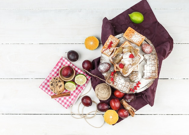 Vista de cima waffles na toalha de mesa cor de vinho com frutas cítricas, clew, canela e tigela de ameixas na superfície da placa de madeira branca. Foto gratuita