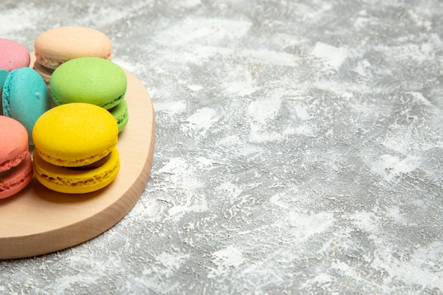 Vista de frente macarons franceses bolos coloridos na superfície branca torta de bolo de açúcar biscoito biscoitos doces Foto gratuita