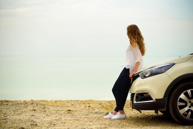 Vista, de, mulher jovem, viajante, olhar, mar, pôr do sol, sentando, ligado, hatchback, car Foto Premium