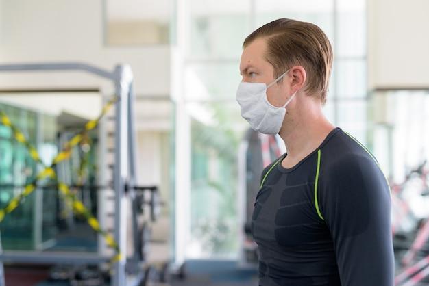 Vista de perfil de jovem com máscara para proteção contra surto de coronavírus na academia durante coronavírus covid-19 Foto Premium