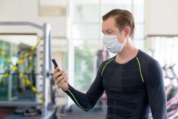Vista de perfil de jovem com máscara usando o telefone na academia durante o coronavírus covid-19 Foto Premium