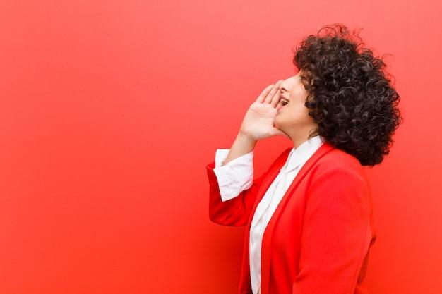 Vista de perfil de mulher jovem e bonita afro, olhando feliz e animado, gritando e chamando para copiar o espaço ao lado Foto Premium
