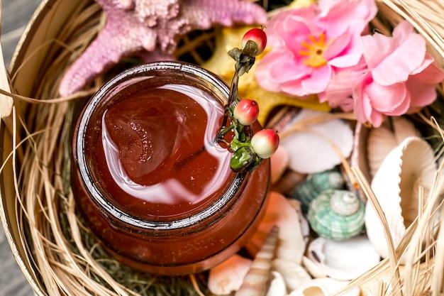Vista de perto do coquetel em jar colocado na caixa com conchas e estrelas do mar Foto gratuita