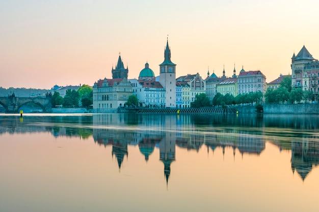 Vista de praga pelo rio, amanhecer na ponte charles ao lado do castelo Foto Premium