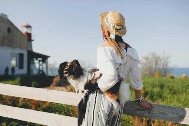 Vista de trás para a frente mulher elegante no campo, segurando um cachorro, humor positivo e feliz, verão, chapéu de palha, roupa de estilo boêmio, Foto gratuita