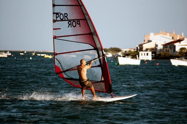 Vista de um adepto de windsurf nas águas do algarve. Foto Premium