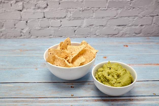 Vista, de, um, tigela, com, condimentado, guacamole, perto, um, tigela, nachos Foto Premium