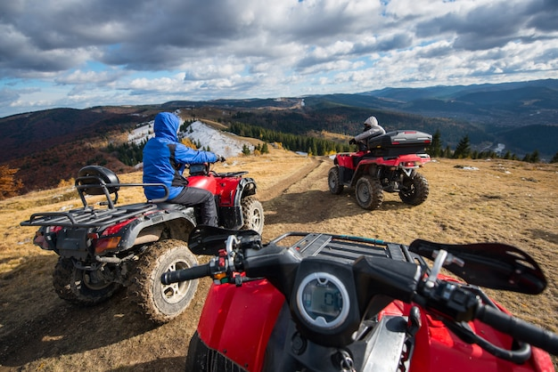 Vista de uma moto-quatro com homens dirigindo um atv em frente no topo da trilha de montanha Foto Premium
