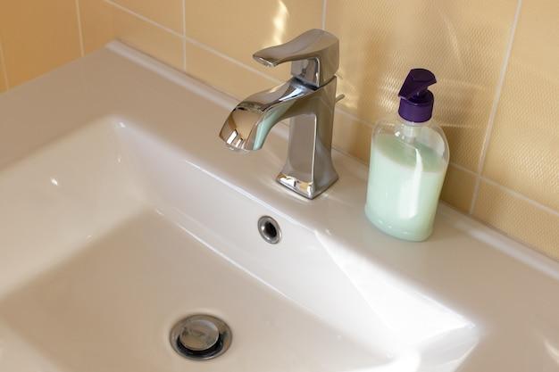 Vista de uma pia de banheiro branca com uma torneira misturadora contemporânea e um frasco de sabonete líquido sem rótulo. conceito de interior moderno, economia de água, higiene diária. vista lateral, close-up. formato horizontal. Foto Premium