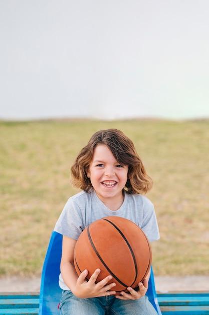 Vista dianteira, de, criança, segurando bola Foto gratuita