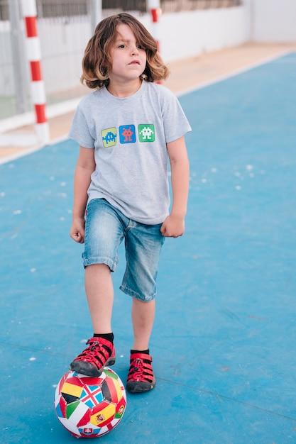 Vista dianteira, de, criança, tocando, com, bola Foto gratuita