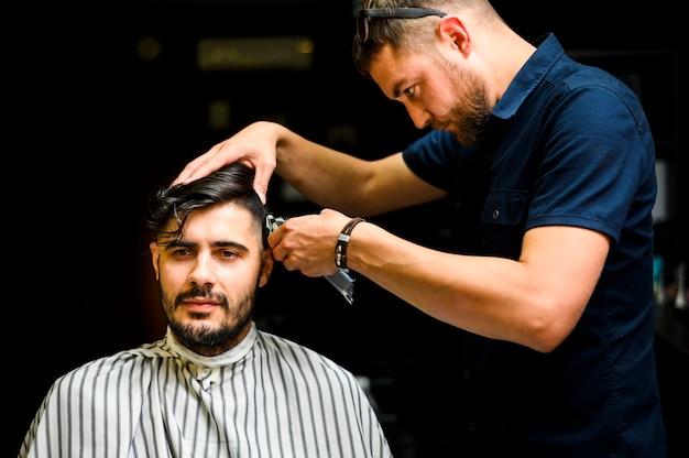 Vista dianteira, de, homem, obtendo, um, corte cabelo Foto gratuita