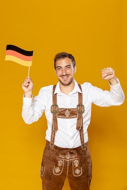 Vista dianteira, de, homem, segurando, bandeira alemã Foto gratuita