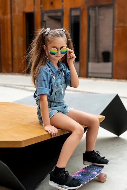 Vista dianteira, de, menina, com, skateboard, e, óculos de sol Foto gratuita