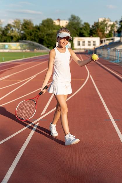 Vista dianteira, de, menina, jogando tênis Foto gratuita