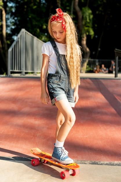 Vista dianteira, de, menina, ligado, skateboard Foto gratuita