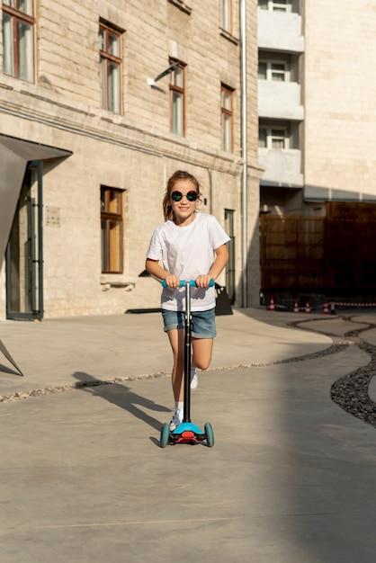 Vista dianteira, de, menina, montando, azul, scooter Foto gratuita